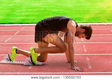 Composite image of sportsman waiting on the starting line on athletics field
