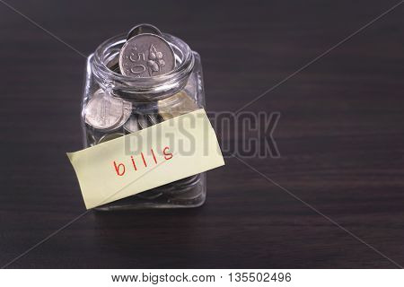 Finacial concept. Money in the glass on wooden table with bills word and copy space area.