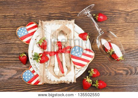 Tableware and silverware with strawberry and cookie on the wooden background