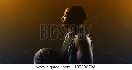 One side of a basketball player holding a basketball against a blackboard