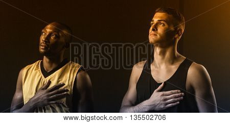 Portrait of basketball players looking up and putting hand on heart on a gym