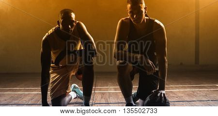 Portrait basketball players posing on their knees on a gym