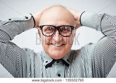 Portrait of a happy elderly man looking at camera in glasses