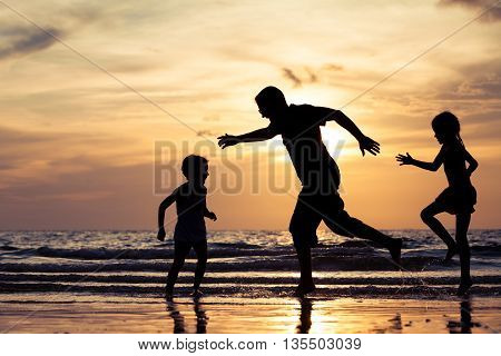 Father and children playing on the beach at the sunset time. Concept of happy friendly family.