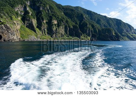 green hill near water in hokkaido japan on view from moving ship