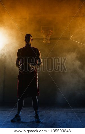 Portrait of a basketball player holding a ball in his hands in a gymnasium