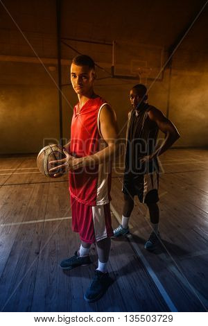 Portrait of two basketball players posing on gym