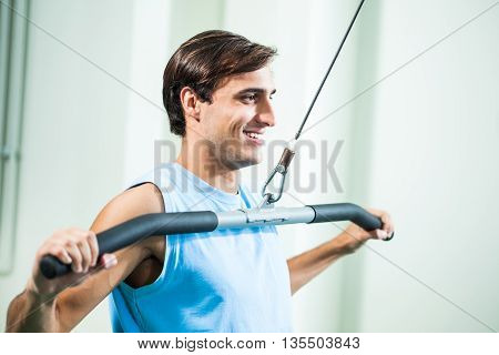 Happy man is exercising in gym. He is building his chest muscles.
