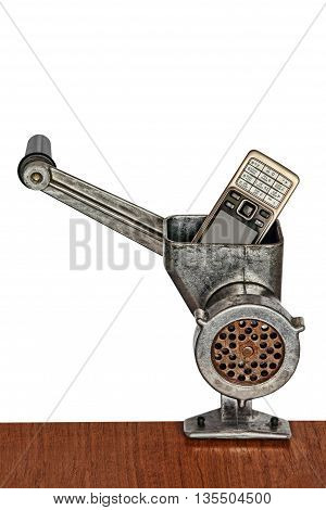 Old mobile phone in meat grinder on white background.Toned image.