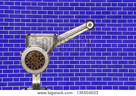 Metal meat grinder on blue brick wall background taken closeup.