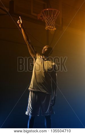Basketball player pointing up with his finger on a gym
