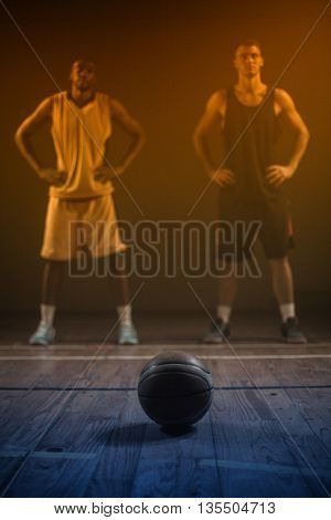 Basketball players posing with hands on hips behind a ball on a gym