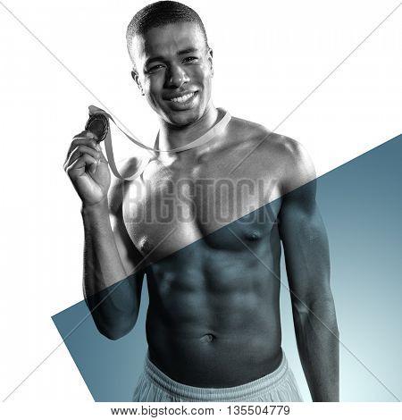 Sportsman holding gold medal against grey vignette