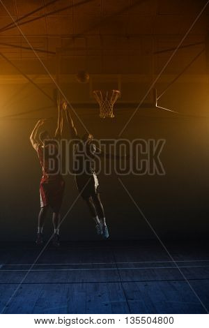 Two basketball player : one shooting, one jumping and trying to block