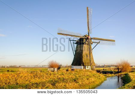 Old thatched windmill in a Dutch polder. The mill was built in 1700. It's a sunny day in winter. A thin layer of ice is on the water.