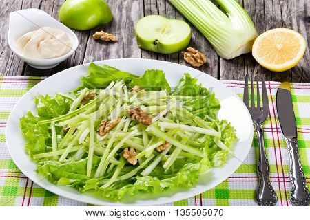 Studio macro of Waldorf Salad on a white dish on a table napkin with fork and knife authentic recipe halves of lemon and apple celery and mayo in a gravy boat on a wooden background close-up view from above