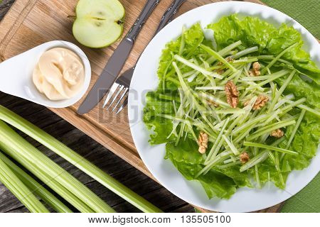 Waldorf Salad with green apples celery and walnuts on a white dish classic recipe view from above