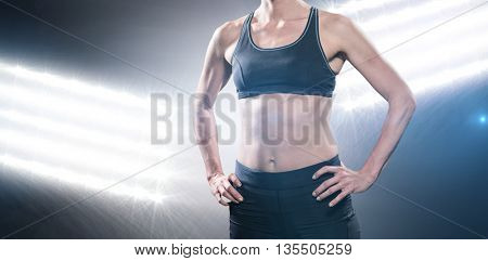 Female athlete standing with hand on hip against spotlights