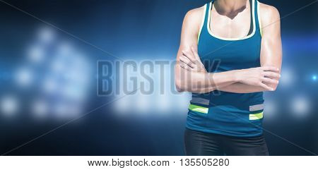 Sportswoman posing and smiling on a white background against composite image of spotlight