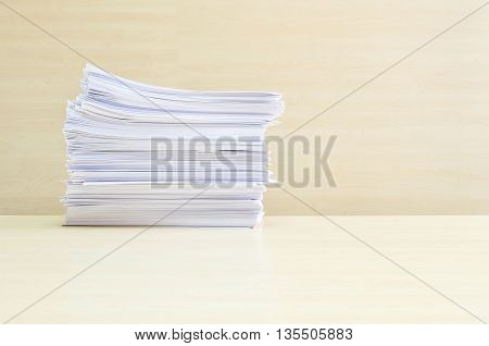Closeup pile of work paper on blurred wooden desk and wall textured background in the meeting room under window light hard work concept