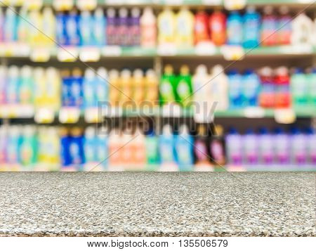 Marble board empty table in front of blurred background. Perspective marble over blur colorful supermarket products on shelves. Mock up for display or montage of product