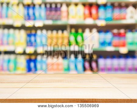 Wooden board empty table in front of blurred background. Perspective light wood over blur colorful supermarket products on shelves. Mock up for display or montage your products.