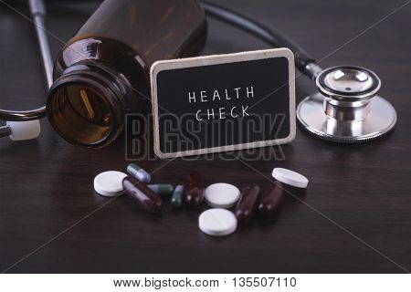 Stethoscope pill bottle Various pills capsules and HEALTH CHECK on wooden background with copyspace area.