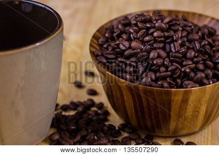 Wooden bowl full of dark coffee beans next to a coffee mug. Shallow depth of field.
