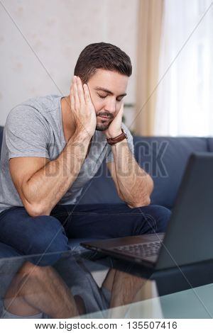 Man sleep in front of laptop at home