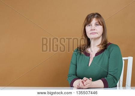 Cute Woman Sitting At A Table..