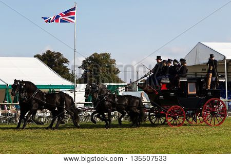NEWBURY, UK - SEPTEMBER 21: Passengers and working crew display there preserved vintage stagecoach in the main arena for the public to view at the Berks County show on September 21, 2014 in Newbury