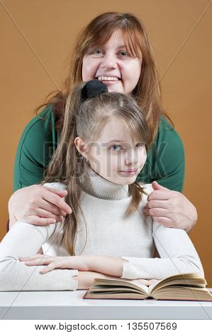 Woman Hugging Her Daughter Sitting With A Book..