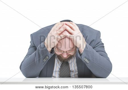 A Man In A Jacket Holding His Head, Sitting At The Table. In Isolation..