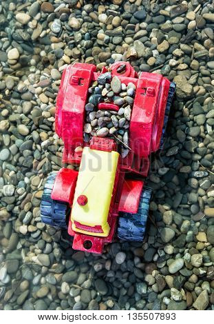 Colorful toy tractor and pebbles in the water. Outdoor toy. Retro toy. Leisure activity. Preschool game theme. Nobody scene.
