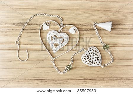 White hanging decoration with hearts on the wooden background. Beautiful symbolic object. Gift of love. Valentine's Day.