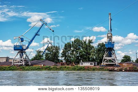 Blue cranes in cargo port translating coal. Industrial scene. Big port-cranes. Danube river.