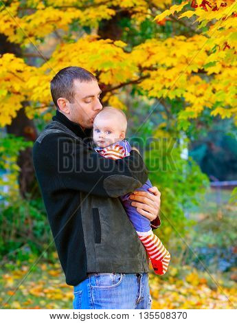 Young Father Kisses The Baby's Forehead. Autumn Landscape