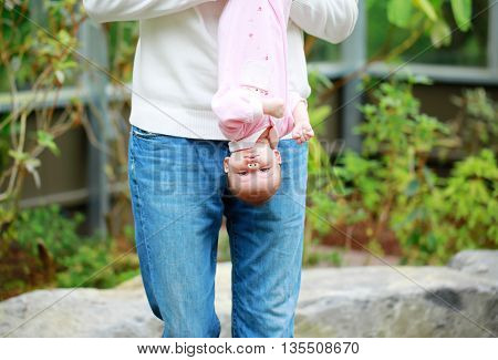 Dad holds the baby upside down outdoor. Cute small girl in pink dress