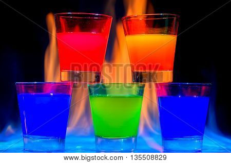 Five different colorful cocktails with flames around