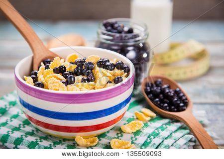 cornflake wth fresh ripe bilberry and milk in crockery dish
