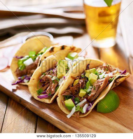 mexican pork carnitas tacos on yellow corn tortilla.