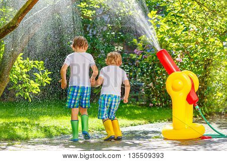 Two funny little friends playing together and splashing with a garden hose on hot and sunny summer day. Two boys having fun outdoors. Funny outdoors leisure wth water for children.