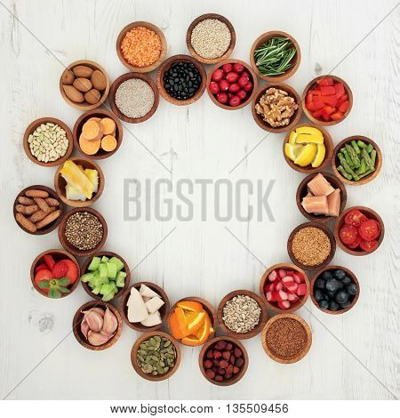 Healthy super food selection in wooden bowls forming a wheel over distressed white wood background. High in antioxidants, vitamins, minerals and anthocyanins.