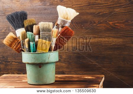 Different colorful brushes in the bucket on the table wooden background