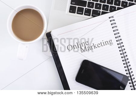 A note book with Online Marketing word and computer smart phone coffee cup. Top view with copy space