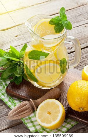 Lemonade pitcher with lemon, mint and ice on garden table