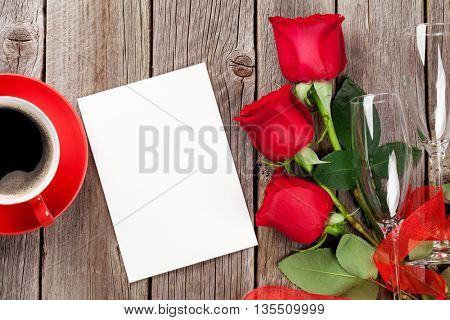 Valentines day greeting card, coffee cup and red roses on wooden table. Top view with copy space