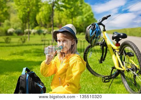 Teenage girl biker sitting on a green grass next to a mountain bike and drinking water