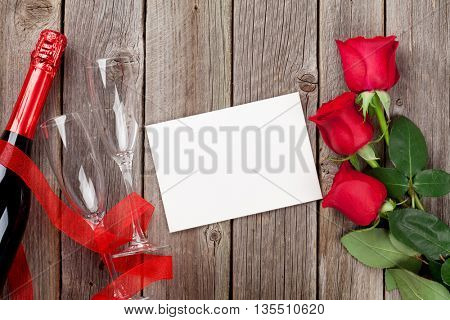 Red roses, champagne and blank greeting card over wooden background. Top view with copy space