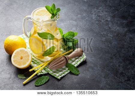 Lemonade with lemon, mint and ice on stone table. View with copy space